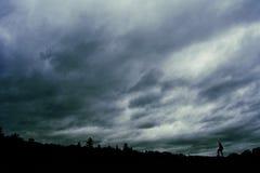 Драматические облака с уединённой персоной в силуэте стоковые фотографии rf