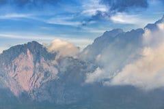 Драматический взгляд лесистых гор в облаках на заходе солнца, Индонезии стоковые изображения