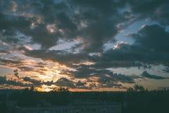 драматический восход солнца над крышей города покрывает - винтажный ретро взгляд Стоковое Фото