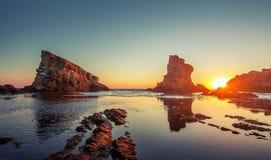 Драматический восход солнца с туманом на пляже с утесами стоковая фотография rf