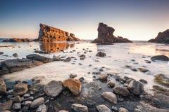 Драматический восход солнца с туманом на пляже с утесами стоковое фото