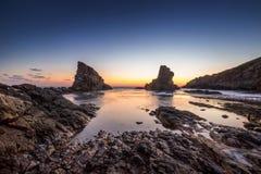 Драматический восход солнца с туманом на пляже с утесами стоковые изображения