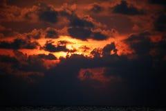 Драматический заход солнца с облаками в оранжевом солнечном свете Пламенеющий заход солнца при свет пропуская через темные облака Стоковое Изображение
