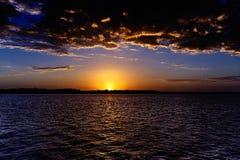Драматическое золото и голубой seascape захода солнца Стоковые Изображения