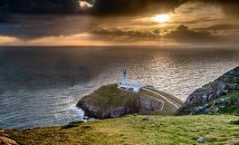 Драматическое небо над историческим южным маяком стога - остров Anglesey северного вэльса Великобритании Стоковое Фото