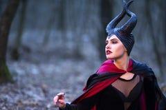 Драма костюма Загадочный Maleficent женский представлять в предыдущем лес стоковое изображение rf
