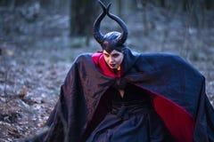 Драма костюма Загадочный Maleficent женский представлять в черном плаще в  стоковое фото rf