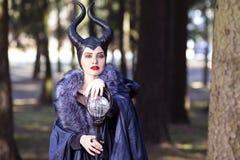 Драма костюма Молодые кавказские женские представления в Maleficent лес од стоковое фото