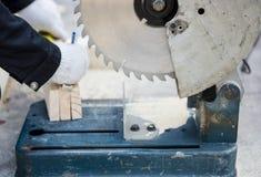 Древесина вырезывания плотника с электрической пилой стоковая фотография