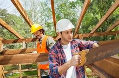 Древесина вырезывания рабочий-строителя с ручной пилой на Стоковая Фотография