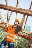 Древесина вырезывания рабочий-строителя с ручной пилой на Стоковые Фотографии RF