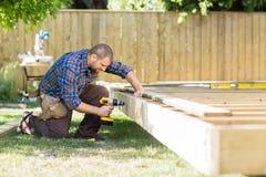 Древесина плотника сверля на строительной площадке стоковое фото
