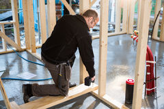 Древесина плотника сверля пока встающ на колени на строительной площадке Стоковые Изображения