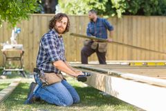 Древесина работника сверля на строительной площадке Стоковые Изображения RF