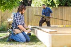 Древесина работника физического труда сверля на строительной площадке Стоковые Фото