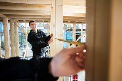 Древесина счастливого плотника измеряя с помощью коллеги на месте стоковое изображение