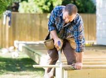 Древесина sawing работника на строительной площадке Стоковые Изображения
