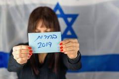 Древнееврейские избрания 2019 текста на бумаге голосования над деревянной доской с предпосылкой confetti стоковое изображение