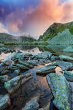 Древнее ледниковое озеро в Альпах и облака шторма на заходе солнца Стоковые Фотографии RF