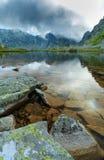 Древнее ледниковое озеро в Альпах и облака шторма на заходе солнца Стоковые Изображения