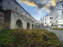 Древняя крепость Pecherskaya Lavra: каменную стену с сводами протягивает вдоль белых зданий, в расстоянии можно увидеть куполам Стоковая Фотография