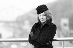 Дресс-код зимы дела на изо дня в день Женщина стоя близко барьера моста в черном пальто Портрет дамы в черноте стоковые изображения rf