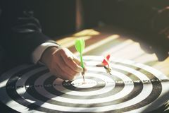Дротик удерживания бизнесмена прикрепленный для нацеливания на dartboard стоковые изображения rf