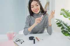 Другое изображение девушки сидя на таблице и смотря к щетке которую она имеет в ее руках Затишье взглядов блоггера Стоковое Изображение