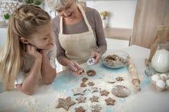 Дружелюбная бабушка и ребенк печь совместно в кухне Стоковая Фотография