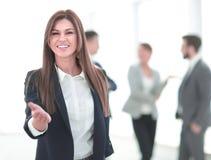 Дружелюбная бизнес-леди держа вне ее руку для рукопожатия стоковое фото