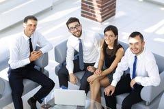 Дружелюбная команда дела сидя в лобби офиса Стоковые Изображения RF