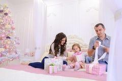 Дружелюбная семья в праздничном настроении для того чтобы обменять подарки сидя на кровати Стоковая Фотография RF