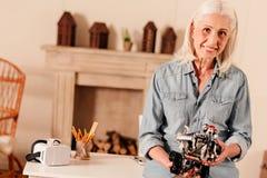 Дружелюбная смотря старшая женщина держа игрушку и усмехаться робота стоковое фото rf