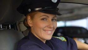 Дружелюбное женщина-полицейский усмехаясь и смотря к камере, сидя в патрульной машине, заказ сток-видео