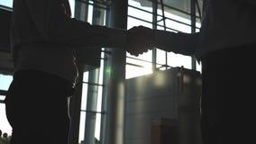 Дружелюбное рукопожатие 2 бизнесменов приветствуя один другого в офисе Рукопожатие дела крытое Трясти мужских оружий акции видеоматериалы