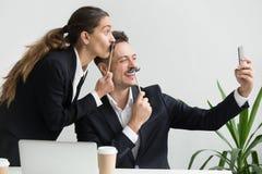 Дружелюбные коллеги гримасничая держащ поддельный усик принимая selfi Стоковые Изображения RF