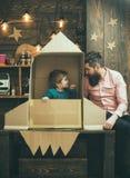 Дружелюбные отношения положительная семья астронавтов Отец и сын играют стоковая фотография rf
