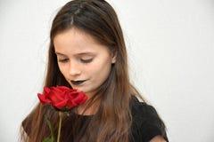 Дружелюбный девочка-подросток с чернотой покрасил губы и красную розу стоковые фото