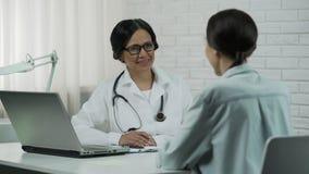 Дружелюбный доктор говоря к пациенту, обещающ, что помогло, сообщая хорошие результаты сток-видео