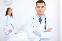 Дружелюбный мужской доктор на предпосылке женского врача в офисе больницы Стоковое Фото
