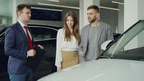 Дружелюбный продавец автомобилей говорит к уверенно молодому человеку говоря ему о новой модели корабля пока милая женщина сток-видео