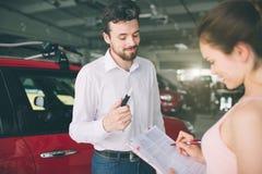Дружелюбный продавец автомобилей говоря к молодой женщине и показывая новый автомобиль внутри подписания выставочного зала контра стоковые фото