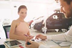 Дружелюбный продавец автомобилей говоря к молодой женщине и показывая новый автомобиль внутри подписания выставочного зала контра стоковое фото