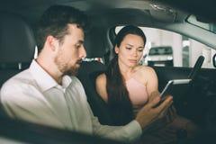 Дружелюбный продавец автомобилей говоря к молодой женщине и показывая новый автомобиль внутри подписания выставочного зала контра стоковое изображение