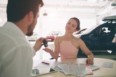 Дружелюбный продавец автомобилей говоря к молодой женщине и показывая новый автомобиль внутри подписания выставочного зала контра стоковая фотография