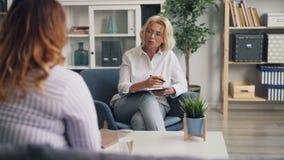Дружелюбный psychotherapist говоря с брюзгливой девушкой усмехаясь во время консультации сток-видео