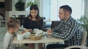 Дружелюбная европейская семья тратя время совместно в кафе Папа играя с дочерью пока она штепсельная вилка ` s ждать мама сток-видео