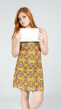 Дружелюбная девушка держит бумагу в руке Copyspace Redheaded wea девушки Стоковое Изображение RF