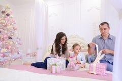 Дружелюбная семья в праздничном настроении для того чтобы обменять подарки сидя на кровати Стоковые Изображения RF
