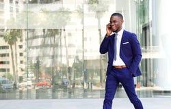 Дружелюбный африканский бизнесмен говоря на мобильном телефоне Стоковые Изображения